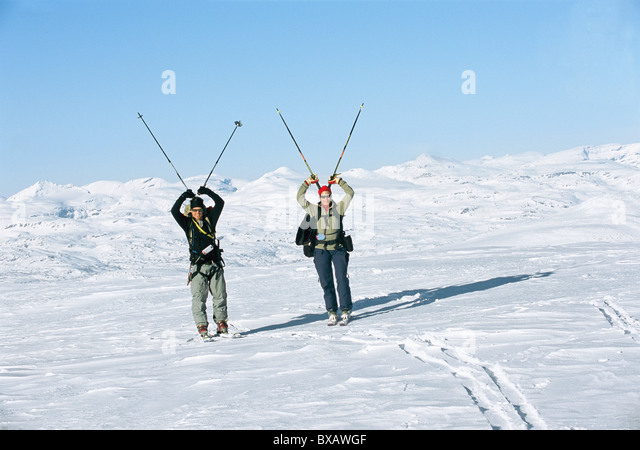 Tourists carrying ski poles - Stock Image