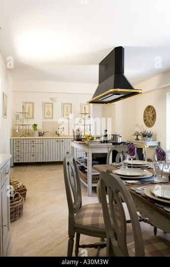 Open plan kitchen diner with checked patterned chairs at table setting - Stock Image