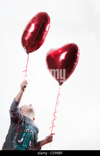 young boy holding a heart shaped balloon - Stock Image