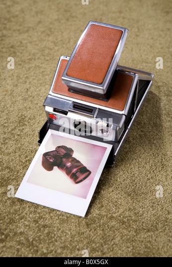 A Polaroid camera with a Polaroid picture of a digital camera - Stock Image