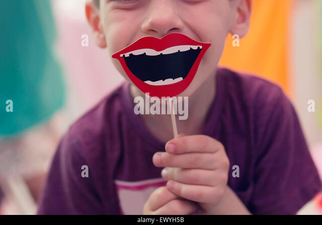 Boy holding a smile prop on a stick - Stock Image