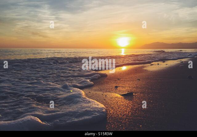 Sunset over a sandy beach with waves - Stock Image