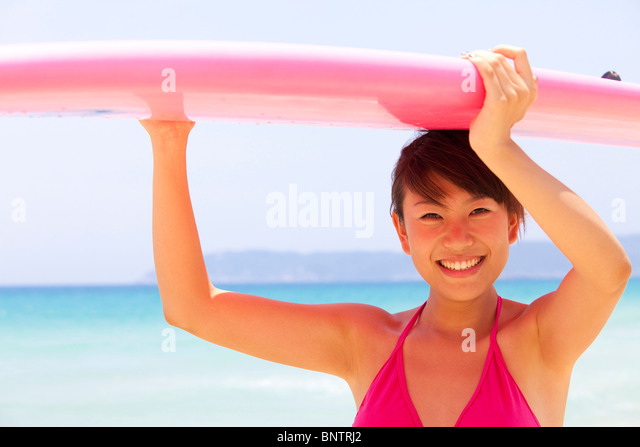 Portrait of a young woman with a surfboard - Stock Image