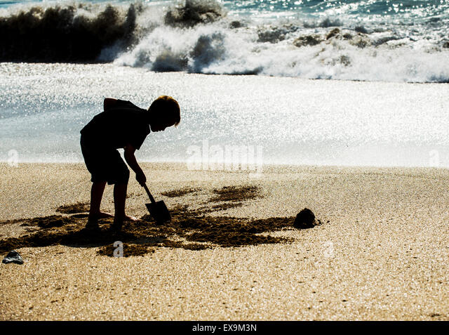 The silhouette of a young boy digging in the sand on Fistral Beach in Newquay, Cornwall. - Stock Image