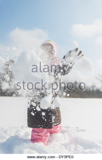 Young girl in deep snow throwing a snowball - Stock Image