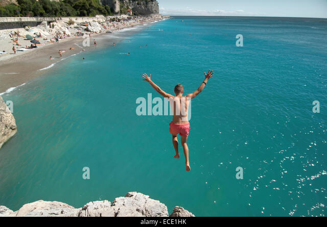 Boy holiday jump water ocean risk teenager - Stock Image