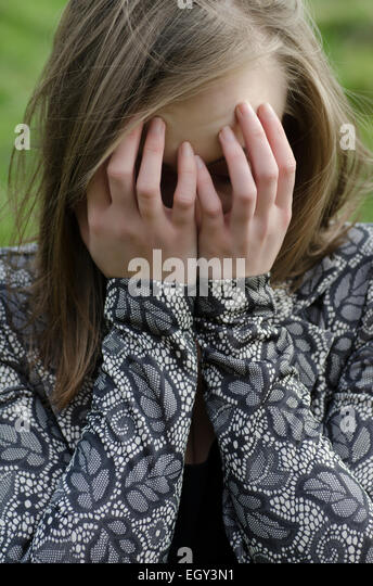Young woman head in hands crying outdoors - Stock Image