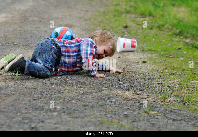 A little boy, crying as he trips over - Stock Image