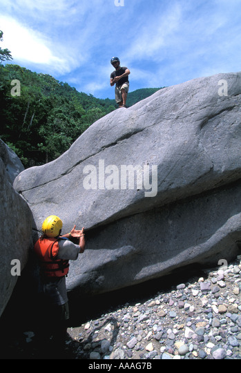 Honduras Cangrejal River whitewater rafting climbing rocks during rest stop boulders vertical Central America - Stock Image