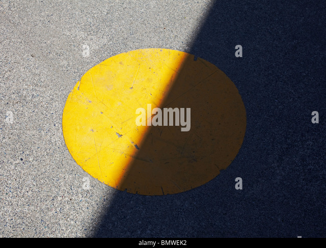 painted yellow spot on sidewalk in half shadow - Stock Image