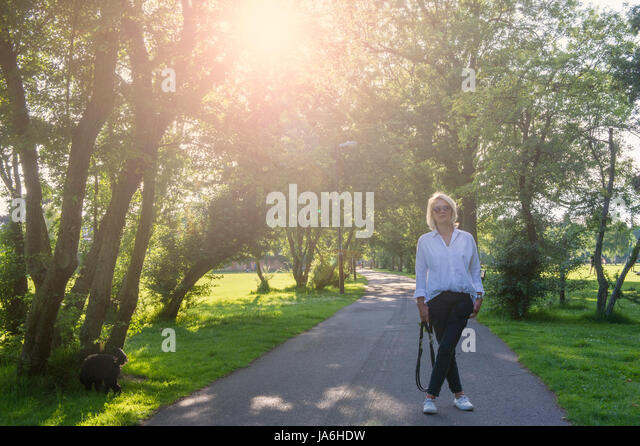 A woman looks for her dog on a walk in a London park - Stock Image