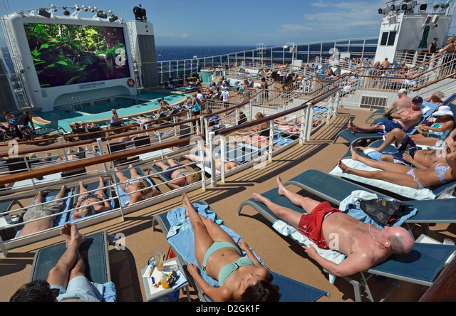 Passengers sunbathing at sea on the aft deck of the cruise ship Norwegian Epic. - Stock Image