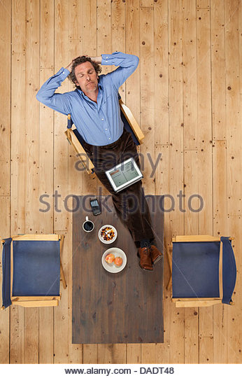 Overhead view of male relaxing with feet up in studio space - Stock Image
