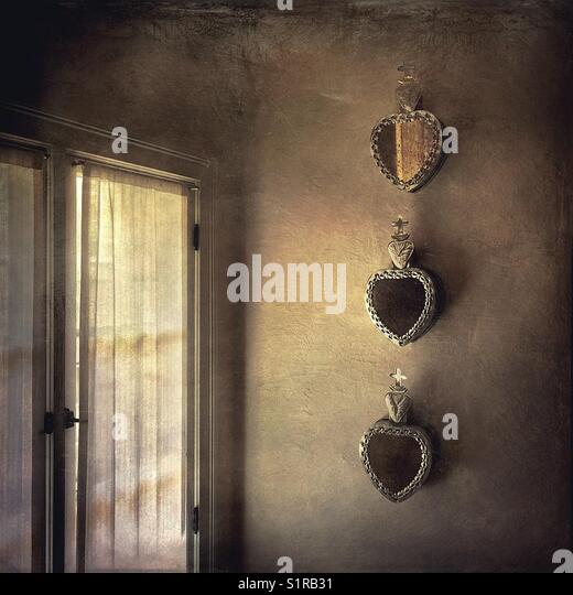 Textured vintage treatment of three tin sacred hearts/sacre de couer hanging on a stucco wall next to a window with - Stock Image