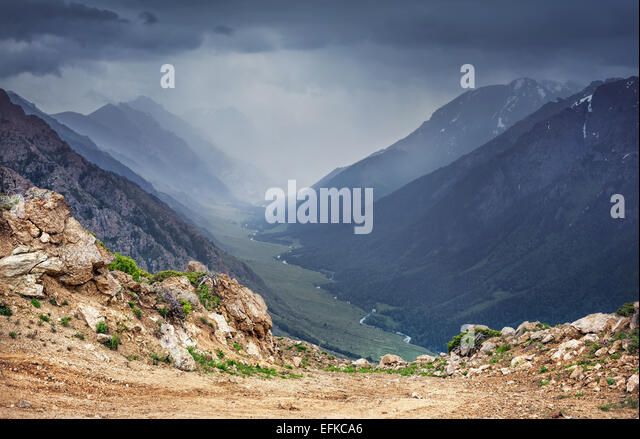 Mountain valley with river and overcast grey sky in Dzungarian Alatau Kazakhstan, Central Asia - Stock Image
