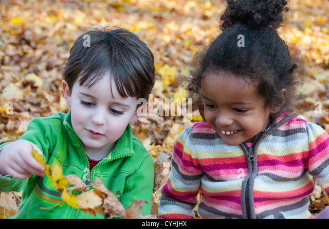 Two children playing in leaves - Stock Image