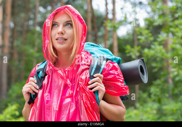 Beautiful backpacker in raincoat looking away at forest - Stock-Bilder