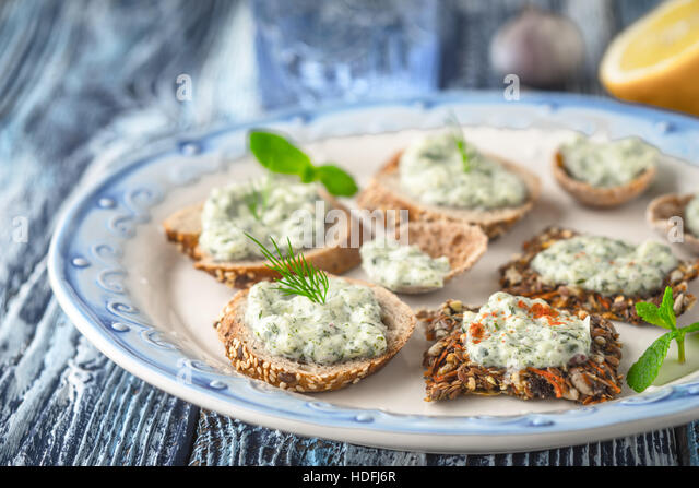 Plate with different bread with tzatziki on the blue table horizontal - Stock Image