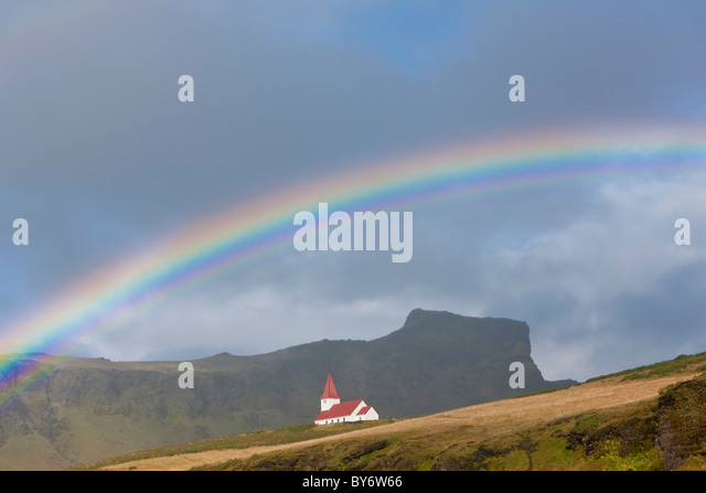 Rainbow over church, Vik, Iceland - Stock-Bilder
