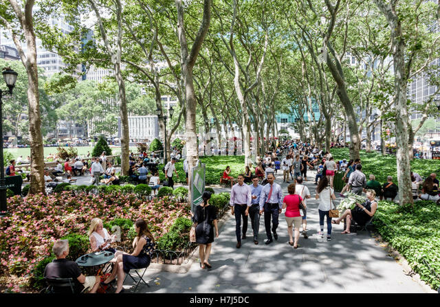 New York New York City NYC Manhattan Midtown Bryant Park public park trees man woman lunch crowd walking - Stock Image