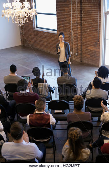 Businesswoman with microphone leading conference meeting - Stock Image