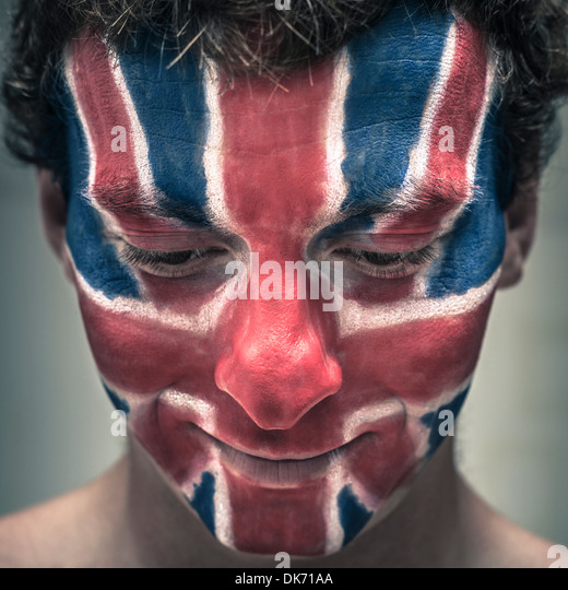 Closeup of smiling man with British flag painted on face looking down. - Stock Image