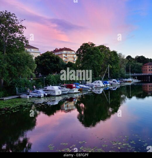 Sweden, Stockholm, Boats at jetty in summer at sunset - Stock Image