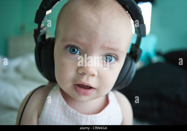 One year old girl wearing large headphones and looking wide-eyed. - Stock Image