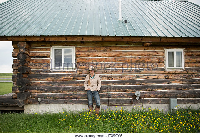 Portrait female rancher standing against cabin wall - Stock Image