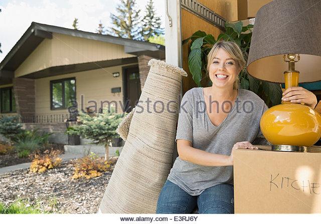 Portrait of woman unloading belongings from moving van - Stock Image