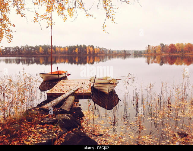 Sweden, Boats at tranquil lake - Stock Image
