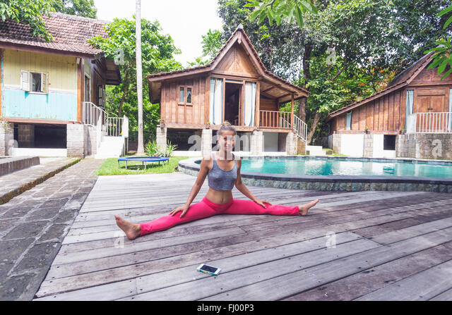 Indonesia, Bali, woman practising yoga at the poolside - Stock Image