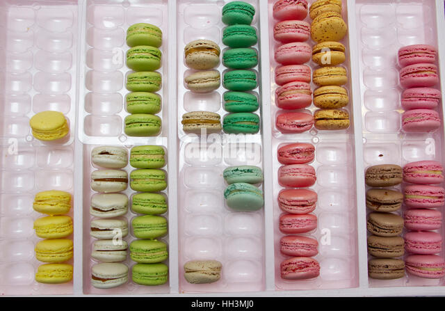 Brightly coloured/colored biscuits/cookies in a display rack - Stock Image