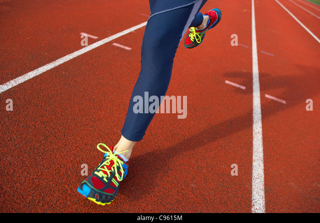 Running. Close-up of the legs of a woman running on an athletics track. - Stock Image