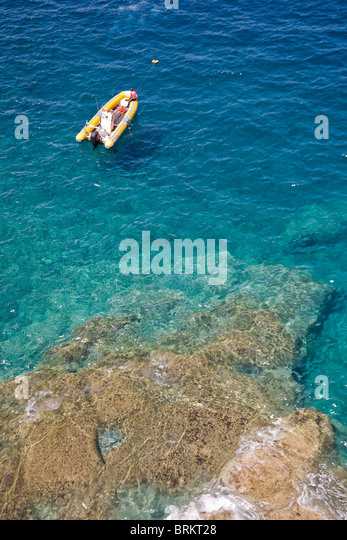 Dive boat off the south coast of Gran Canaria photographed from the cliffs above Amadores beach - Stock Image