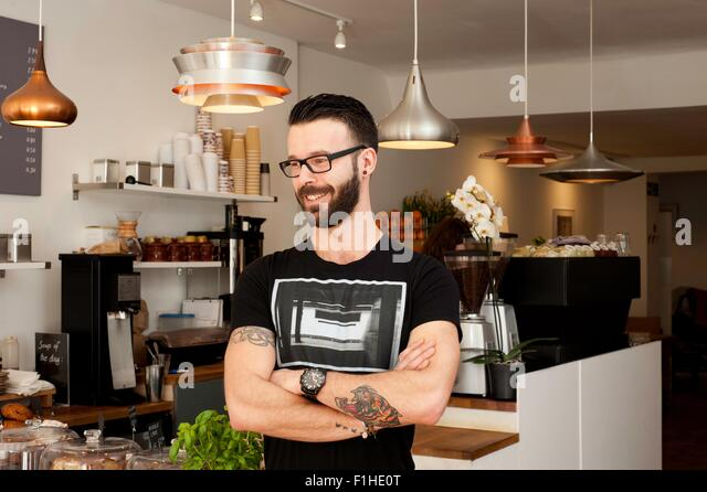 Portrait of cafe waiter with arms folded - Stock Image