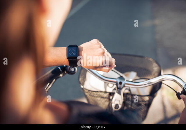Hand of a woman with smartwatch. Close up shot of female on bicycle checking time on her smart wristwatch. - Stock Image