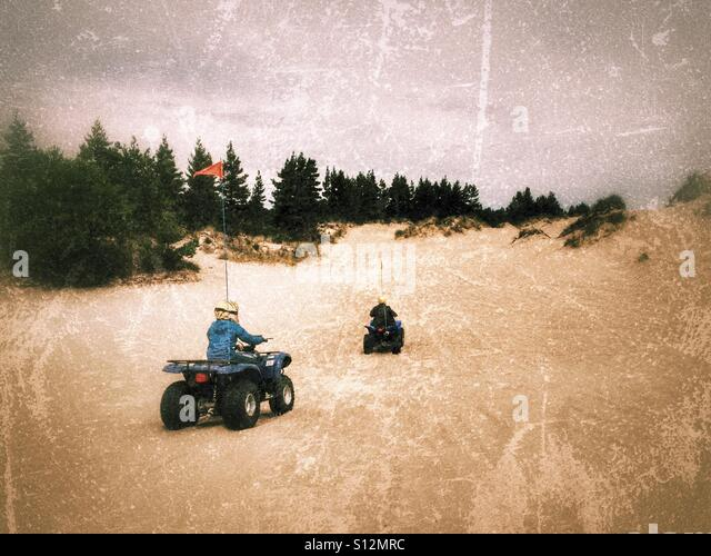 Two quad riders in the sand dunes of Oregon, USA. - Stock Image