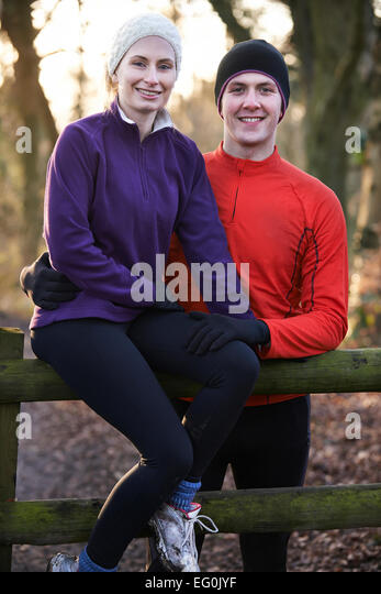 Portrait Of Couple On Winter Run Through Woodland Sitting On Fence - Stock Image