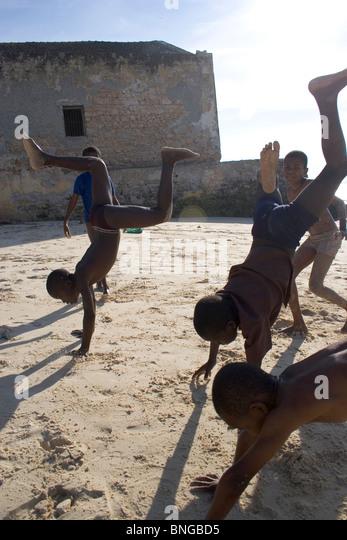 Mozambican boys doing handstands on the beach, Ilha de Mozambique, Mozambique - Stock Image