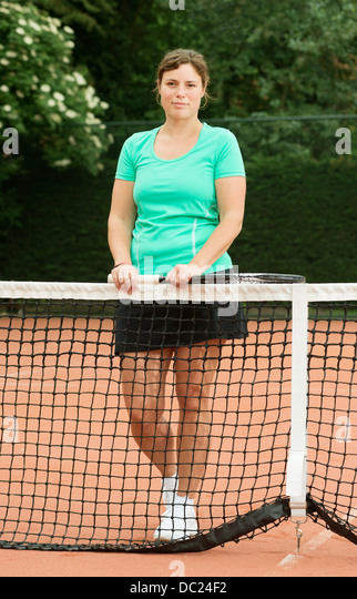 Woman standing beside tennis net - Stock Image