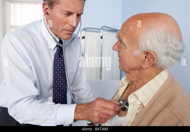 Medical consultation. General practitioner using a stethoscope to examine an elderly patient. - Stock Image