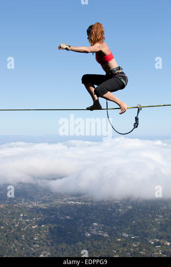 Professional highliner Hayley Ashburn stands up on a highline above the clouds atop Mount Tamalpais - Stock Image