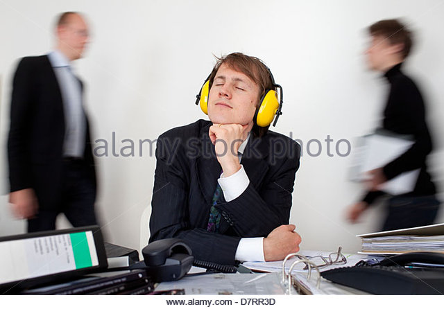 Businessman wearing ear defenders and day dreaming with his colleagues in the background - Stock Image