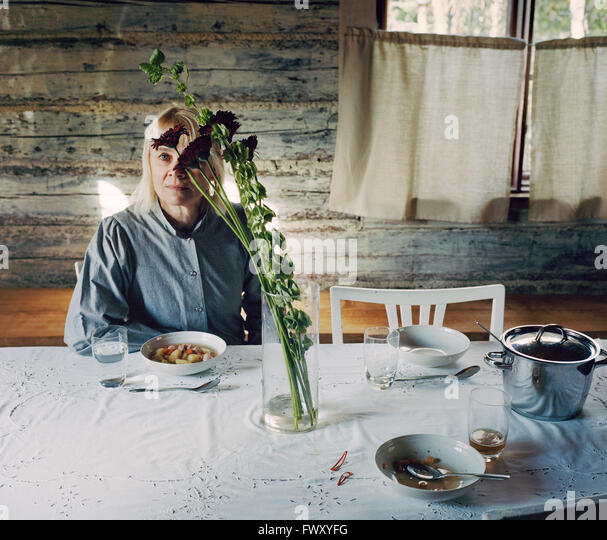 Finland, Mature woman sitting at table - Stock-Bilder
