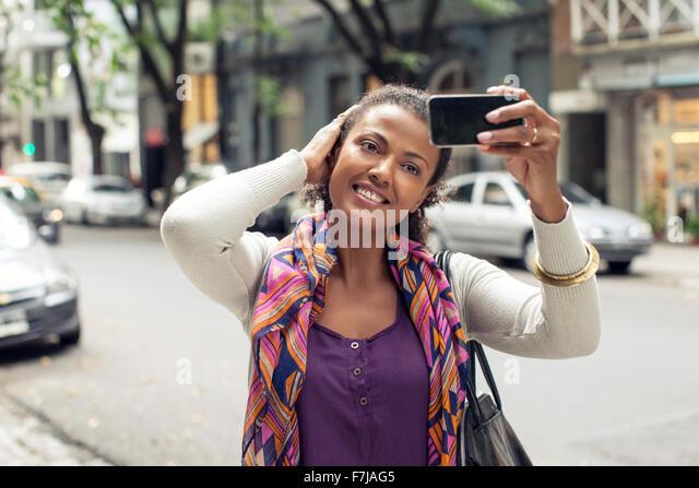 Woman taking selfie on street - Stock Image