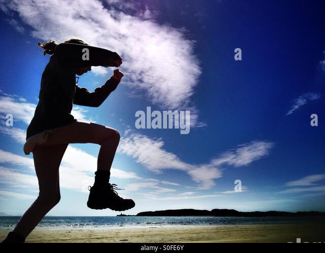 Girl jumping on beach - Stock Image