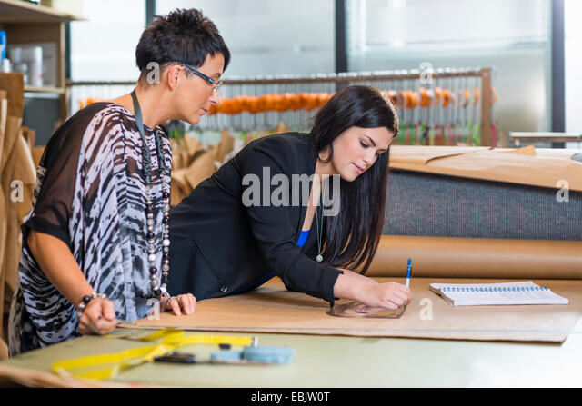Two seamstresses drawing dressmakers pattern in workshop - Stock-Bilder