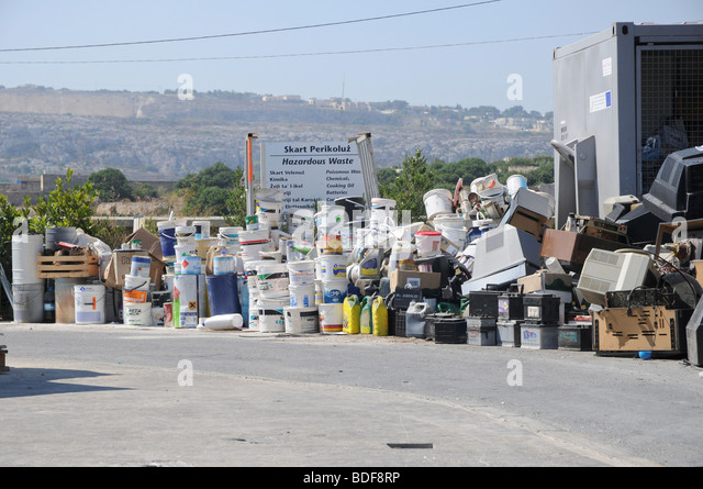Paint buckets and fuel containers ready to be recycled at a waste management plant in Malta. - Stock Image