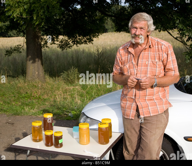 Man selling honey at side of road Poland - Stock Image